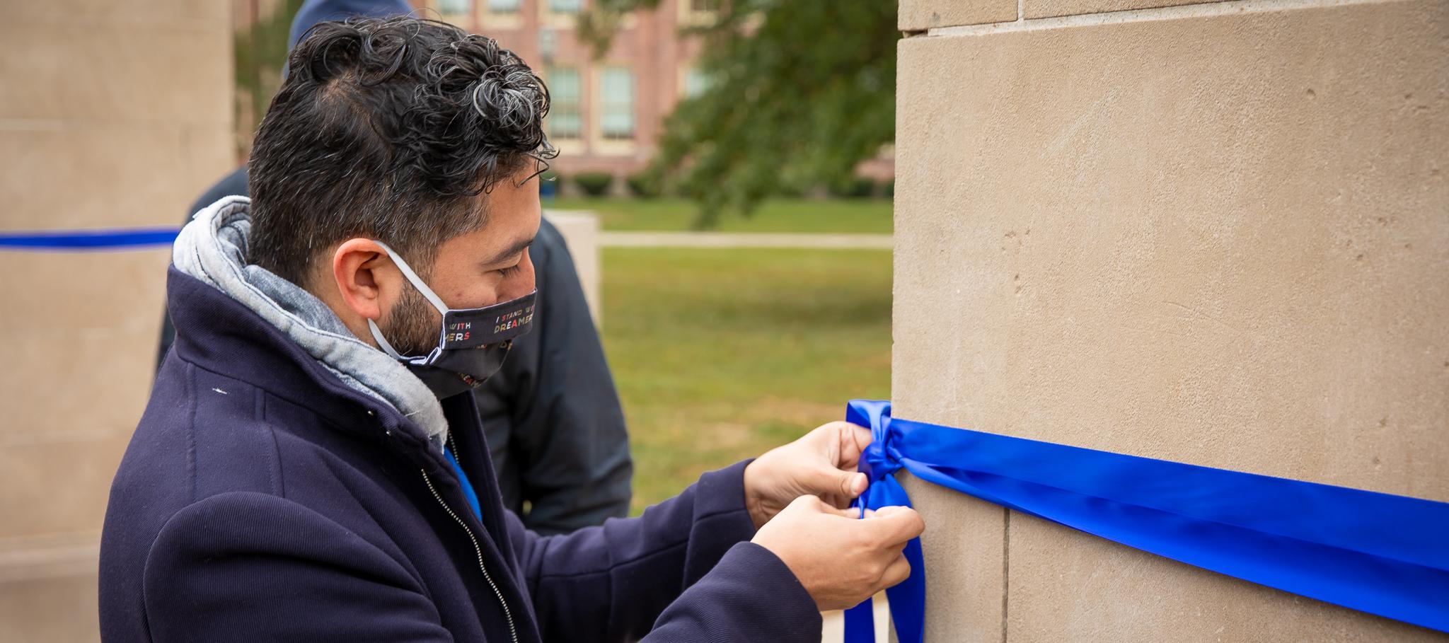 Board President tying blue ribbon